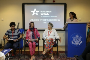 Special guest, Ilona Yusuf (second from left) joins EdUSA Adviser, Heba Al-Adawy (right), and first prize winner, Eeman Khalid at the podium during the awards ceremony in Islamabad.